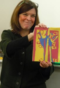 Nancy Rourke holding up an ILY tree artwork made from paper